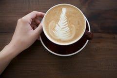 Kop van cappuccino met lattekunst op houten lijstachtergrond stock afbeelding