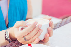 Kop van cappuccino in vrouwelijke handen Stock Foto