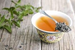 Kop van Chinese thee op een houten achtergrond met munt Stock Afbeelding