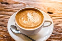 Kop van de koffie van de lattekunst met lepel en plaat op de bruine achtergrond van de schors mooie textuur met warm licht Stock Afbeeldingen