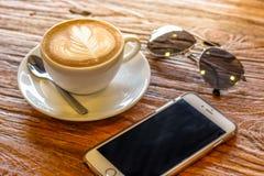 Kop van de koffie van de lattekunst met lepel en plaat op de bruine achtergrond van de schors mooie textuur met warm licht Stock Afbeelding