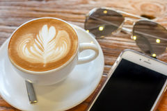 Kop van de koffie van de lattekunst met lepel en plaat op de bruine achtergrond van de schors mooie textuur met warm licht Royalty-vrije Stock Afbeeldingen