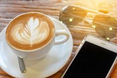 Kop van de koffie van de lattekunst met lepel en plaat op de bruine achtergrond van de schors mooie textuur met warm licht Stock Fotografie