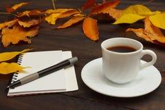 Kop van espresso, notitieboekje en pen onder de herfstbladeren op houten achtergrond stock afbeelding