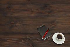 Kop van espresso, pen en zwart notitieboekje op houten Desktop Mening van hierboven stock foto's