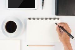 Kop van heet koffie en mensenhand het schrijven notitieboekje op witte backgr Royalty-vrije Stock Foto