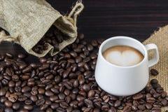 Kop van het hartvorm van de koffie latte kunst met de achtergrond van koffiebonen Stock Fotografie