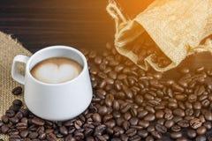 Kop van het hartvorm van de koffie latte kunst met de achtergrond van koffiebonen Koffieachtergrond met licht Stock Afbeeldingen