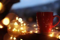 Kop van hete die drank op balkontraliewerk met Kerstmislichten wordt verfraaid, ruimte voor tekst royalty-vrije stock afbeelding
