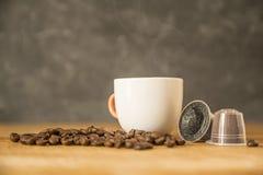 Kop van hete koffie en grondkoffie in capsules van koffiebonen op een houten lijst van een rustieke keuken Rook, aroma stock afbeelding