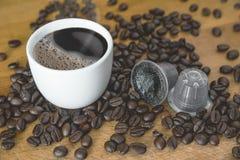 Kop van hete koffie en grondkoffie in capsules van koffiebonen op een houten lijst van een rustieke keuken Rook en aroma stock foto