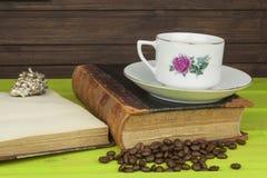 Kop van hete koffie en oud boek Het ontspannen bij de koffie Het bestuderen van oude boeken Plaats voor uw tekst Stock Foto