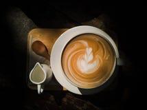 Kop van hete koffie met hart latte art. Hoogste mening met warme kleurentoon Favoriete drank in ochtend stock afbeelding