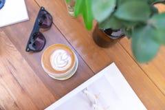 kop van hete melkkoffie met recente kunst op houten lijst, levensstijlconcept stock afbeeldingen