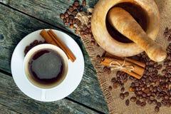 Kop van koffie, bonen en kaneel op een houten achtergrond Houten mortier stock fotografie