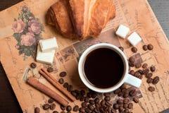 Kop van koffie, croissant, koffiebonen, kaneel en suiker Royalty-vrije Stock Afbeeldingen