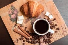 Kop van koffie, croissant, koffiebonen, kaneel en suiker Stock Foto's