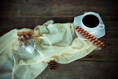 Kop van koffie, denneappels a op houten achtergrond Stock Afbeelding