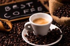 Kop van koffie door koffiebonen die wordt omringd stock fotografie