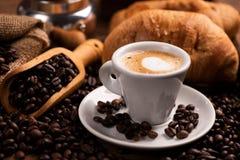 Kop van koffie door koffiebonen die wordt omringd royalty-vrije stock fotografie