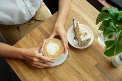 Kop van koffie in een koffie en meisjes` s handen Close-up die van vrouwen` s handen, met kop van koffie in een koffie zitten Royalty-vrije Stock Fotografie