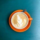 Kop van koffie in een oranje kop op een blauwe achtergrond Stock Afbeeldingen
