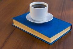 Kop van koffie en boek op houten lijst Stock Foto
