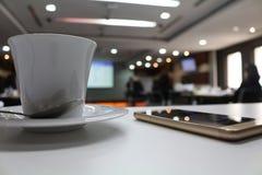 kop van koffie en cellphone in zijvergaderzaal stock afbeelding