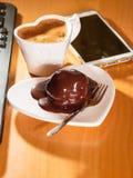 Kop van koffie en chocoladecake naast computer Royalty-vrije Stock Foto's