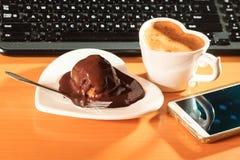 Kop van koffie en chocoladecake naast computer Royalty-vrije Stock Fotografie