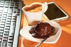Kop van koffie en chocoladecake naast computer Royalty-vrije Stock Afbeeldingen