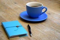 Kop van koffie en een blocnote op een lijst stock fotografie