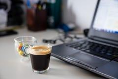 Kop van koffie en kop gekleurde chocolade gevulde snoepjes naast Stock Afbeelding