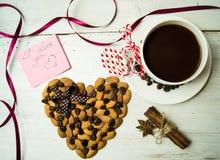Kop van koffie en hart met amandelen op een witte achtergrond Stock Fotografie