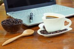 Kop van koffie en laptop op houten lijst Stock Fotografie