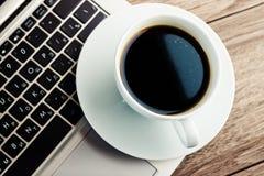 Kop van koffie en laptop op houten lijst Royalty-vrije Stock Foto's