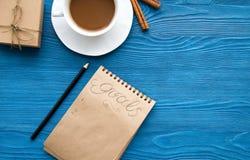 Kop van koffie en notitieboekje met doelstellingen voor nieuw jaar Royalty-vrije Stock Afbeelding