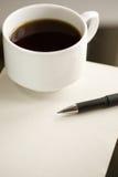 Kop van koffie en pen op het document. Stock Afbeeldingen