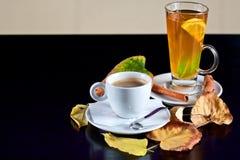 Kop van koffie en thee met de herfstbladeren Stock Foto's