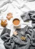 Kop van koffie, grijze warme gebreide sweater overmaatse, gele droge bladeren op het bed - comfortabel huisstilleven stock foto