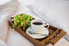 Kop van koffie in houten dienblad op comfortabel bed met hoofdkussen Stock Foto's