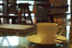 Kop van koffie in koffiewinkel met boek voor lezing Royalty-vrije Stock Afbeeldingen