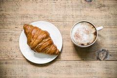 Kop van koffie latte en croissant op houten lijst Royalty-vrije Stock Afbeelding