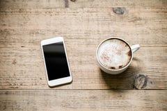 Kop van koffie latte met witte smartphone op houten lijst Stock Afbeelding