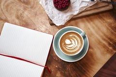Kop van koffie latte op houten lijst of achtergrond van hierboven Het hebben van lunch in koffie Geopend notitieboekje, ruimte vo royalty-vrije stock fotografie