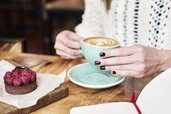 Kop van koffie latte op houten lijst of achtergrond in vrouwenhanden van hierboven Het hebben van lunch in koffie Geopend notitie stock foto