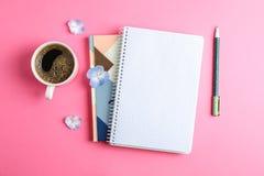 Kop van koffie met bloemblaadjes van bloem, voorbeeldenboeken en pen op kleurenachtergrond royalty-vrije stock afbeeldingen