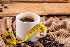 Kop van koffie met bonen en meetlintstilleven stock afbeelding