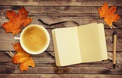 Kop van koffie met droge de herfstbladeren, blocnote en een pen op hout Royalty-vrije Stock Foto's