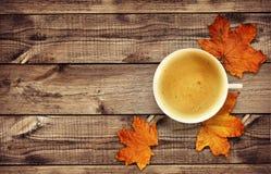 Kop van koffie met droge de herfstbladeren op hout Stock Fotografie